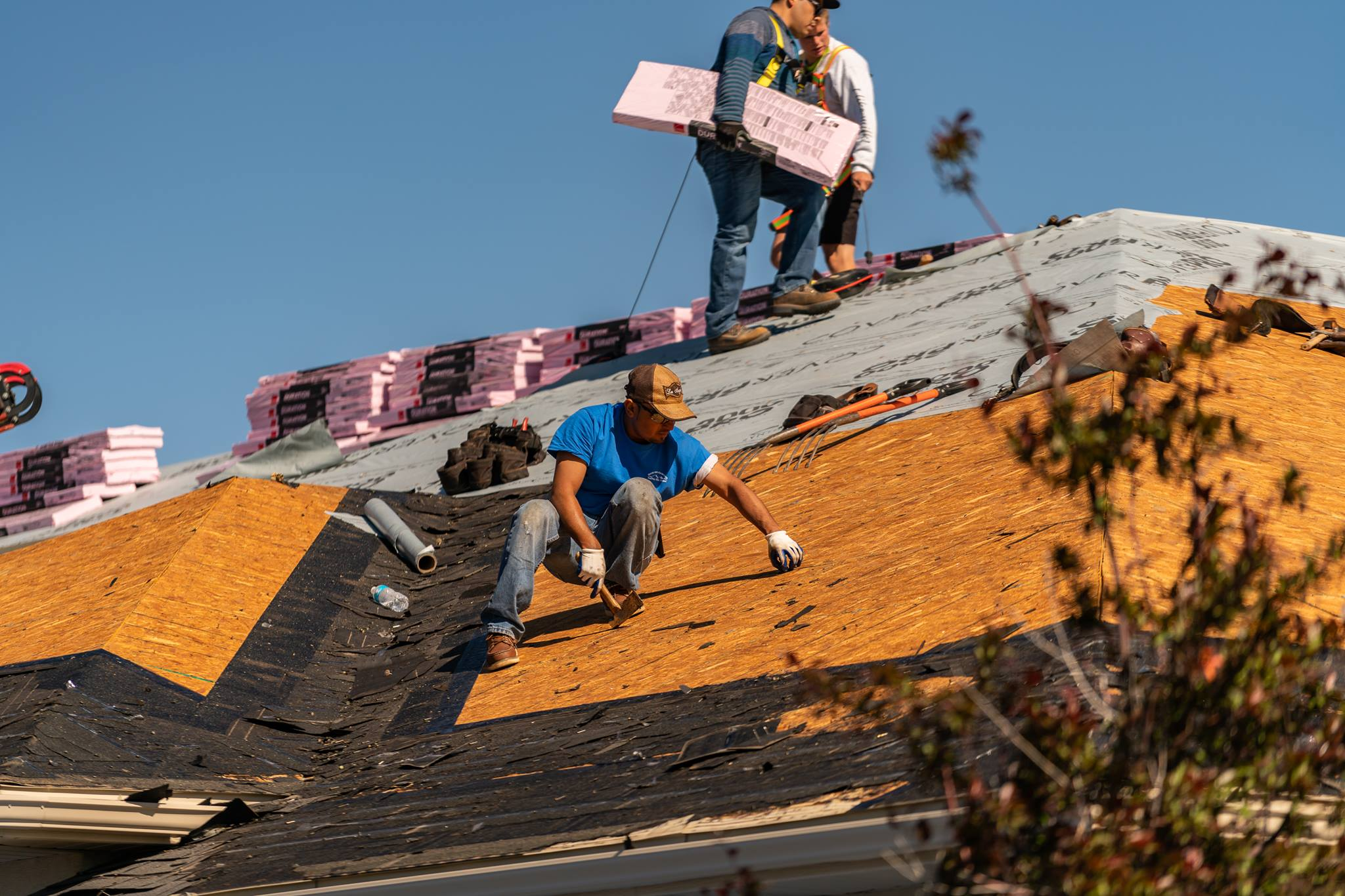 men laying shingles on roof